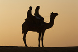 Silhouette Of Two People Atop A Camel At Sunset