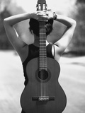 Young Woman Holding an Acoustic Guitar Behind Her Back