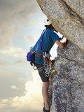 Young man rock climbing up a vertical cliff
