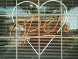 Neon 'Open' sign framed in a heart-shape in a window