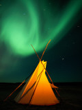 A Solitary Tepee under a Light Streaked Sky from the Aurora Borealis