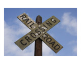 Railroad crossing sign with mold and bullet holes against blue sky