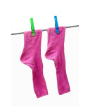 Pink socks with green and blue clothes pins on a washing line