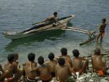 Boys Watch a Man Push Off in an Outrigger Canoe for a Boat Race