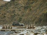 Porters Transport a Car on Long Poles across a Stream