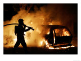 A Firefighter Extinguishes a Car in Les Musicians