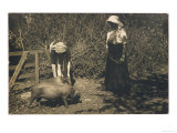 Two Young Women Tend to Pigs in Their Pen
