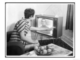 Young Woman with Short Dark Hair Wearing a Stripy Mini Dress Adjusts Her Television Set