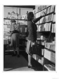 Two Women Both Wearing Box Pleated Skirts Browse Around a Bookshop