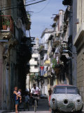 Woman with Baby  Man on Bicycle and Old Car in a Narrow Street Lined with Houses  Havana  Cuba
