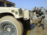 Staff Sergeant Unties a Rope to Tow a Humvee out of the Mud During a Convoy Patrol