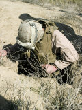 US Marine Jumps Down a Hole Next to a Farm Field North of Hit  Iraq  in Search of a Weapons Cache