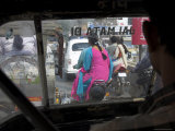 Women Riding on Back of Motorcycles in Heavy Traffic Viewed from Inside a Motor Rickshaw