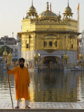 Shrine Guard in Orange Clothes Holding Lance Standing by Pool in Front of the Golden Temple