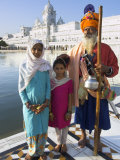 Elderly Couple of Sikh Pilgrims with Young Girl Posing in Front of Holy Pool  Amritsar  India