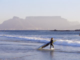 Young Woman Surfer Enters the Water of the Atlantic Ocean with Table Mountain in the Background