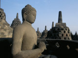 Buddha Image Sitting in Open Chamber with Stupas in Background  Borobudur Temple  Indonesia