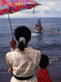 Woman with an Umbrella Watches a Boat Delivering Ashes to the Sea  Bali  Indonesia