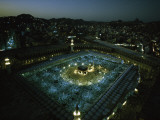 Thousands of pilgrims circle the Kaaba in illuminated view at night