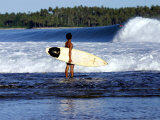 Young Local Boy on Reef Heading out for Afternoon Surf  Lagundri Bay  Indonesia
