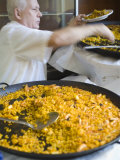 Man Serving Paella  with Noodle Paella in Foreground  Central  Valencia  Spain