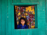 Little Girl in the Window of Her Brightly Painted House  Ciudad Melchor de Mencos  Guatemala