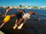 Young Boys Dive Off Marina at Bay of Belize with City in Background  Belize City  Belize