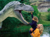 Woman Holding a Girl Up to a Dinosaur Model  Drumheller Valley  Alberta  Canada