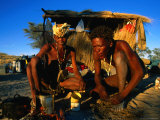 Kalahri Bushmen Cooking on Fire Outside Their Grass Homestead  South Africa