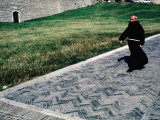 Priest Walks Past a Grassy Lawn in Assisi  Umbria  Italy