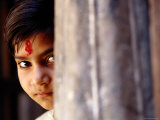 Girl with Forehead Marking Peering from Behind Pillar  Rajasthan  India