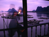 Local Man Lights Pipe Overlooking Net Farms and Karst Formations  Ko Panyi  Phang-Nga  Thailand