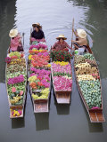 A Group of Four Women Market Traders in Boats Laden with Fruit and Flowers  Thailand