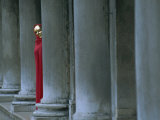 Carnival Model in Red Cape and Gold Mask Peering from Columns in St Mark's Square  Veneto  Italy