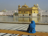 A Pilgrim in Blue Sits by the Holy Pool of Nectar at the Golden Temple  Punjab  India