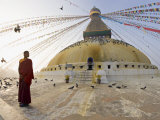Young Buddhist Monk Turns to Look at the Dome of Boudha Tibetan Stupa in Kathmandu  Asia