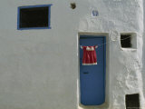Child's Dress Hangs in Front of a Blue Door in a Whitewashed House