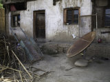 Rusty Satellite Dish and a Rickshaw Cart and Trash Outside a House  Qinghai  China