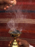Two Hands Burn Traditional Spices in Front of a Decorative Cloth in Petra  Jordan