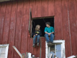 Two Kids Sit in a Barn Window above Discarded Lumber
