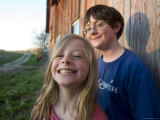 Two Siblings Play near an Old Barn in Nebraska