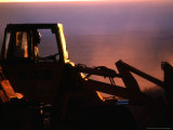 Silhouette of a Man Operating Tractor at Sunset