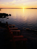 Two Empty Wooden Chairs Sit on Maine's Rocky Coast as the Sun Sets over the Horizon