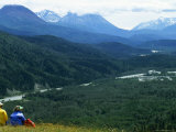 Two Hikers Stop and Relax to Enjoy the Valley View  Alaska