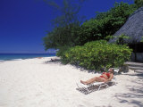 Woman Relaxing on a White Sand Beach in Front of a Bure Hut