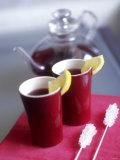 Two Beakers of Fruit Tea with Lemon Wedges  Sugar Sticks
