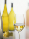 A Glass of White Wine and Wine Bottles in Background