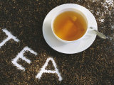 Cup of Black Tea  Surrounded by Tea Leaves with the Word Tea