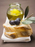 Olive Sprig with Black Olives on White Bread  Olive Oil Behind