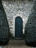 Stone Entry and Wood Door Flanked by Manicured Bushes